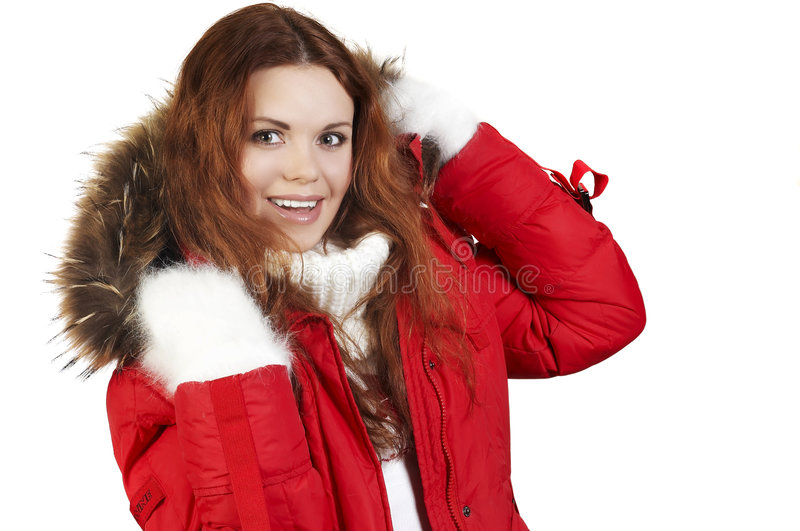 Winter sports jacket. Portrait of the beautiful girl in a red winter jacket and fur collar royalty free stock photo