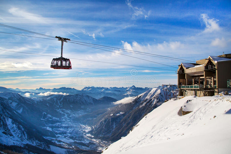 Winter sports travel background with cable car, mountain peaks. Winter sports travel vacation background. Cable Car tram cabin, lift station, high snow mountain royalty free stock image