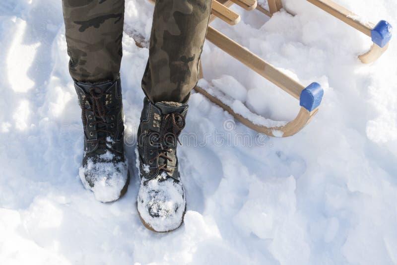Winter-Stiefel auf Schnee Dunkelgrüner warmer Winter lädt Nahaufnahme auf Pferdeschlittenhintergrund auf stockfotografie