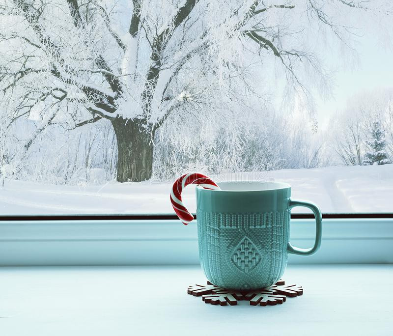 Winter still life - cup with candy cane on windowsill and winter landscape outside, winter composition royalty free stock images