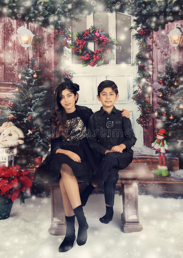 Winter in studio. Siblings dressed up for their christmas photoshoot stock photo