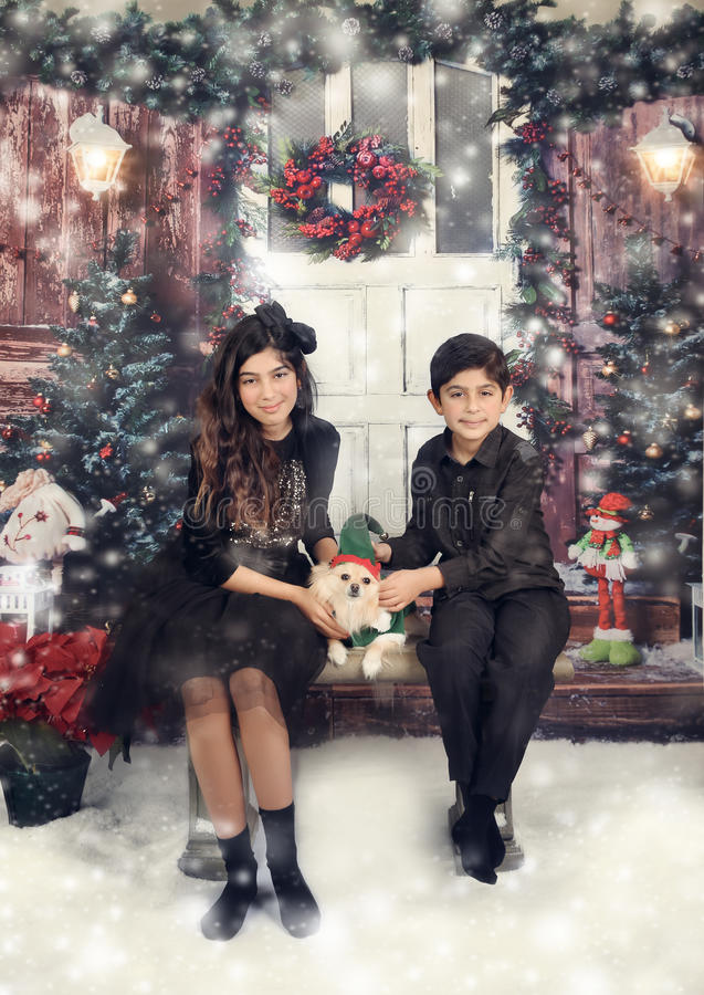 Winter in studio. Siblings and their dog dressed up for their christmas photoshoot stock photography