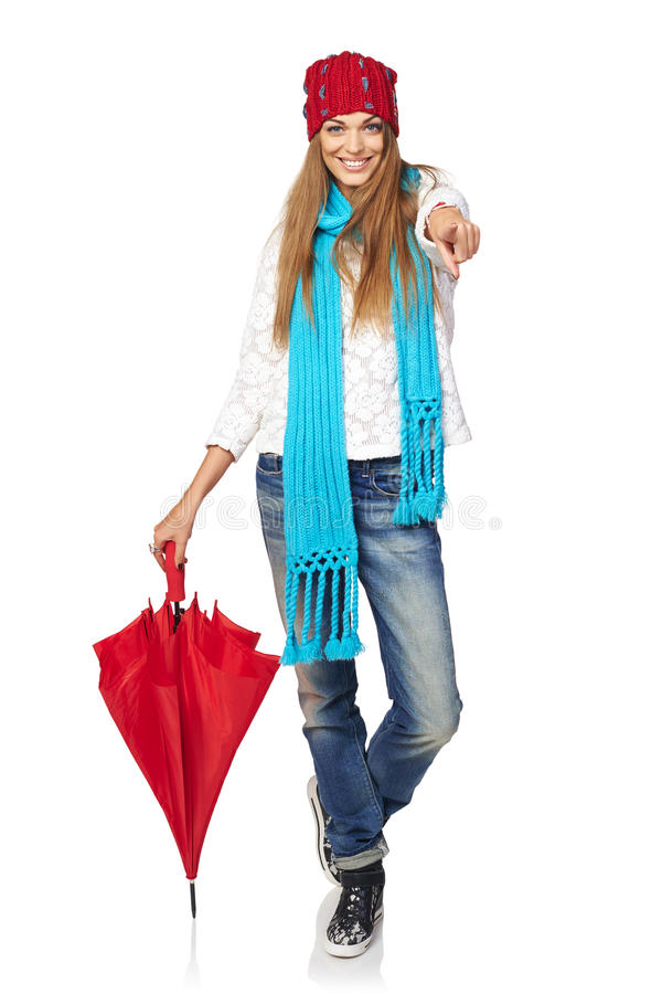Winter style woman portrait. Casual winter style yong smiling woman standing in full length leaning on red umbrella and pointing at you, over white background royalty free stock photography