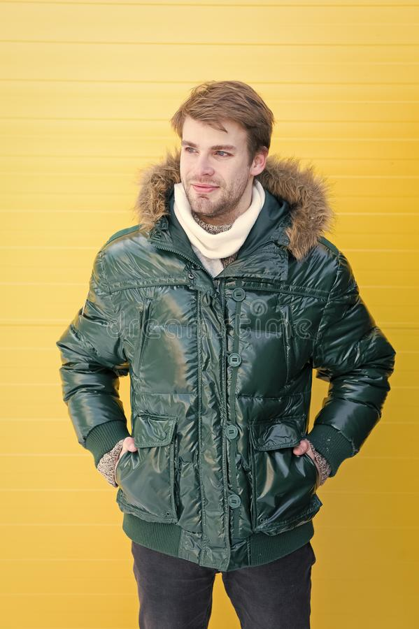 Winter stylish menswear. Man bearded hipster wear warm jacket with fur yellow background. Guy wear warm jacket with hood stock image