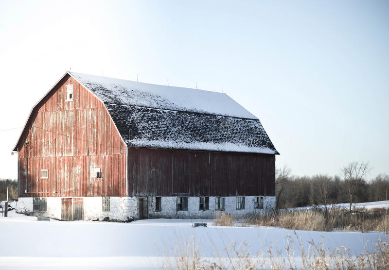 Winter Sun Against the Barn. This picture captures a warm sunset against a stoic barn, on a crisp and still winter evening in Wisconsin stock image