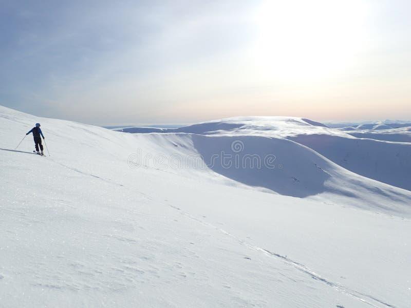 Winter sun over Glas Maol, Glenshee, Highlands, Scotland. Winter sun over Glas Maol, with ski mountaineer on Cairn of Claise in foreground, Glenshee, Highlands stock photos