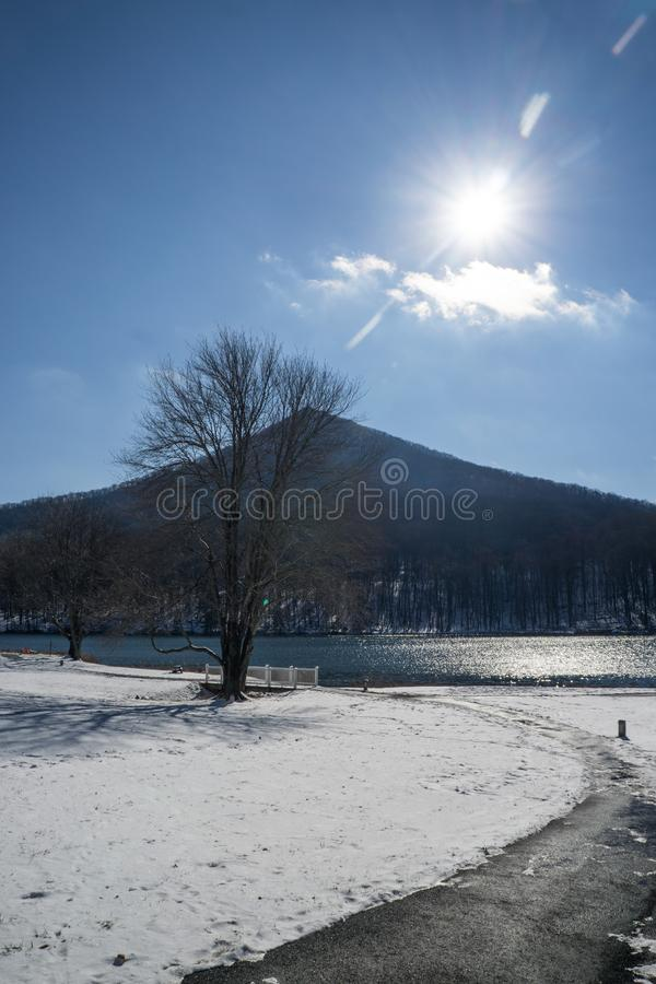 Winter Sun Over Sharp Top Mountain - 2. Winter sun over Sharp Top Mountain with Abbott Lake in foreground located at the Peaks of Otter, Blue Ridge Parkway stock photography