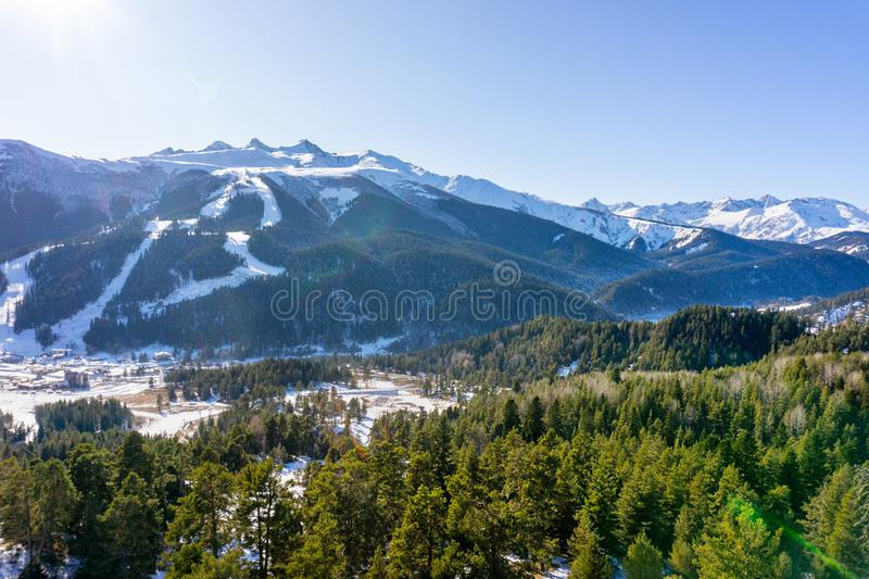 Winter sunny landscape with snowy peaks of mountain ranges with green trees and blue sky.  royalty free stock images