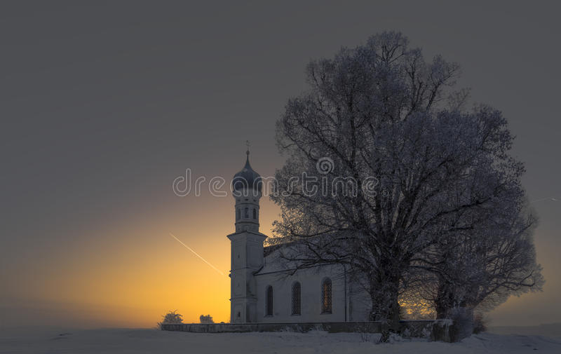 Winter sunrise near the catolic church, fantastic nature landscape, wallpaper stock photography