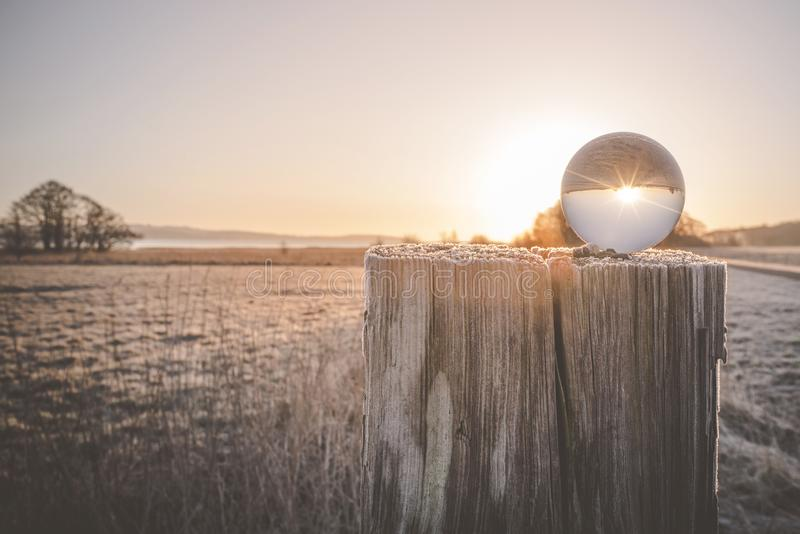 Winter sunrise with sun in a glass orb royalty free stock images
