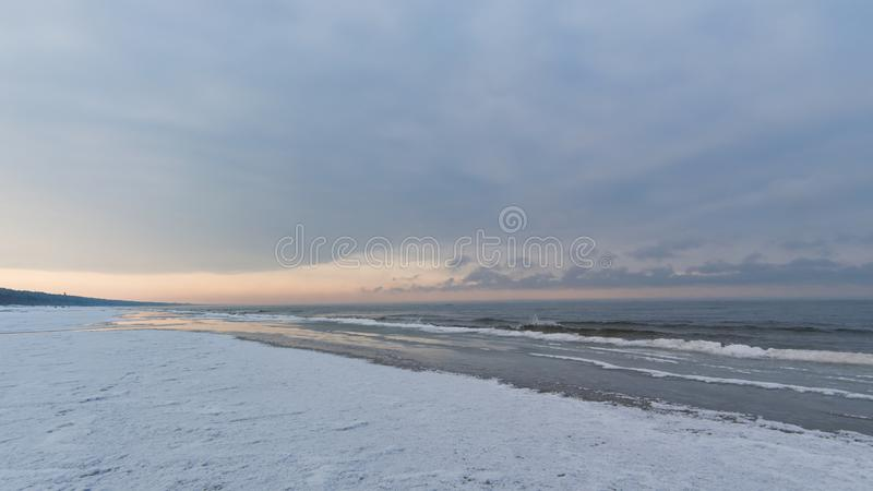 Winter sunset on the Baltic sea shore with snow and ice, selective focus royalty free stock image