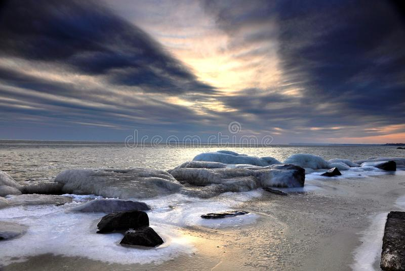 Winter sunset on the Black sea. Winter, dramatic, purple sunset at the sea. Stones in ice stock photography