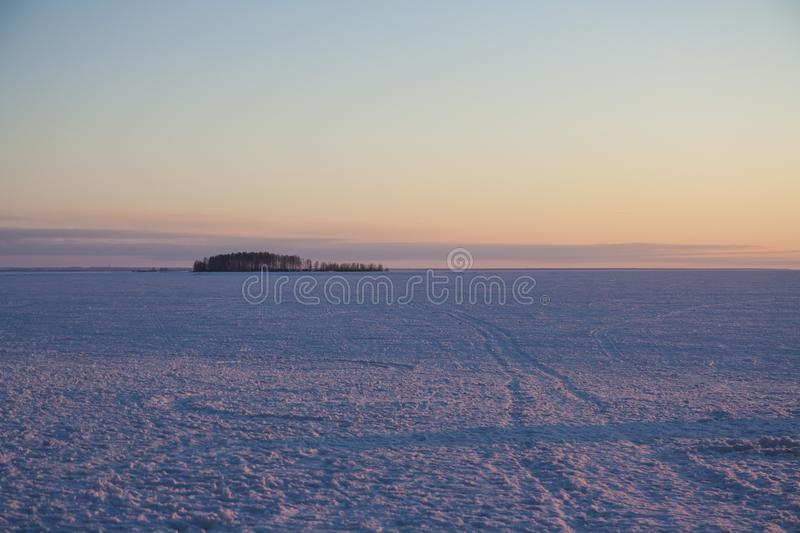 Winter sunset on a frozen snow-covered river. Pink snown stock photos