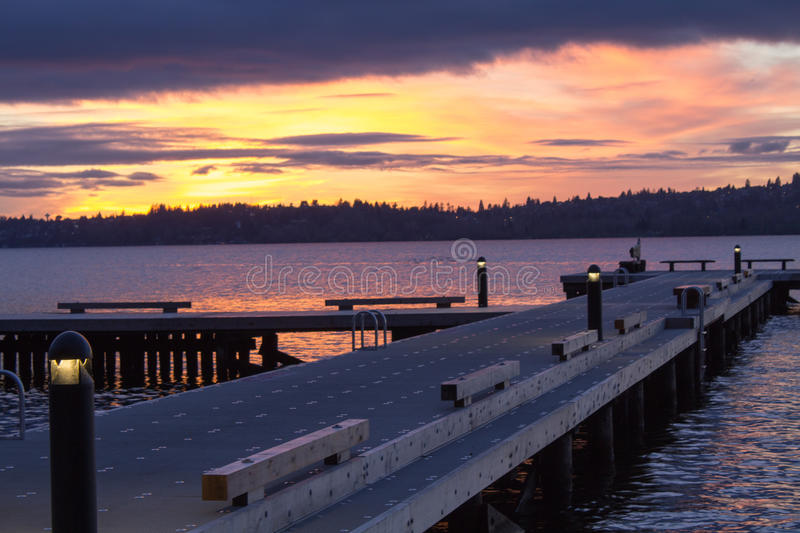 A diagonal view of a pier on a lake in a winter sunset at Waverly Beach Park, Washington, with Seattle skyline in the background royalty free stock photography