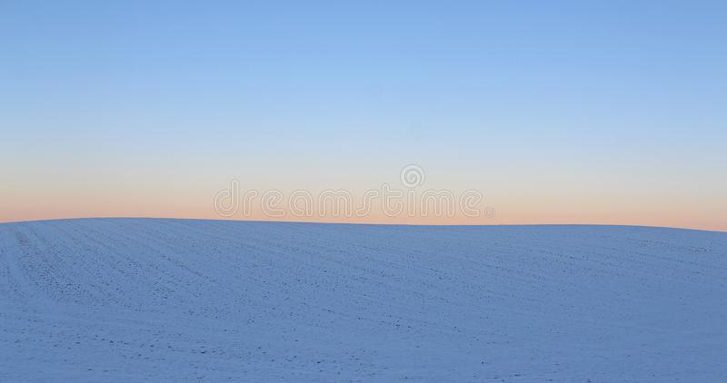 Winter sunset hiding behind a snow field. royalty free stock photos