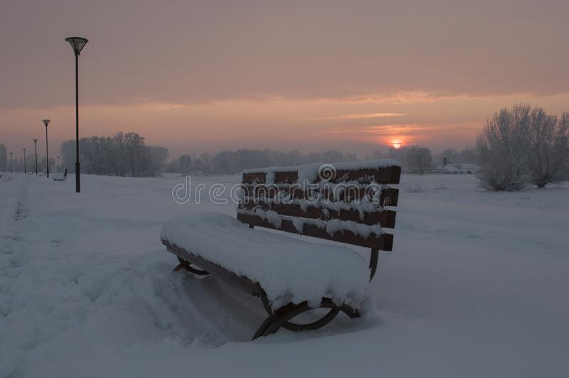 Winter sunset in a huge park with bench covered with snow. And with a lot of snow all around . clouds around the sunlight were between orange and purple shades stock photos
