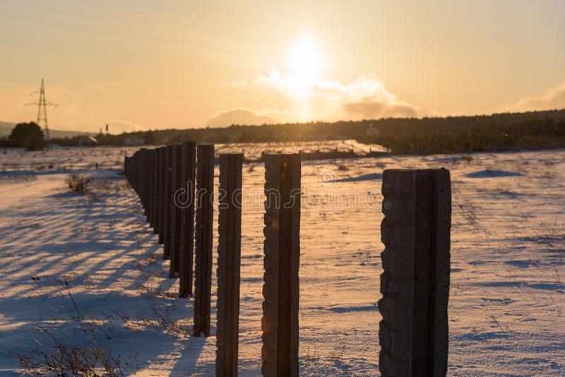 Winter sunset landscape snow covered country fence field. Winter morning landscape dramatic sky snow covered country field royalty free stock photo