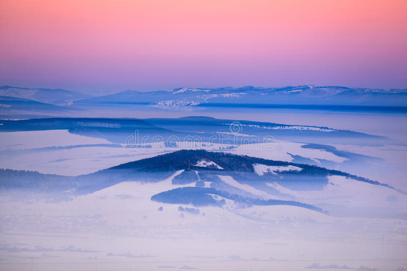 Winter sunset, Romania. Sunset winter scenery in Burzenland Depression in Carpathian Mountains (Brasov, Transylvania in Romania) with snow and fog stock photo