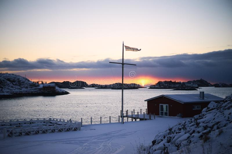 Winter sunset, Scandinavian house, unfrozen sea and low clouds royalty free stock image