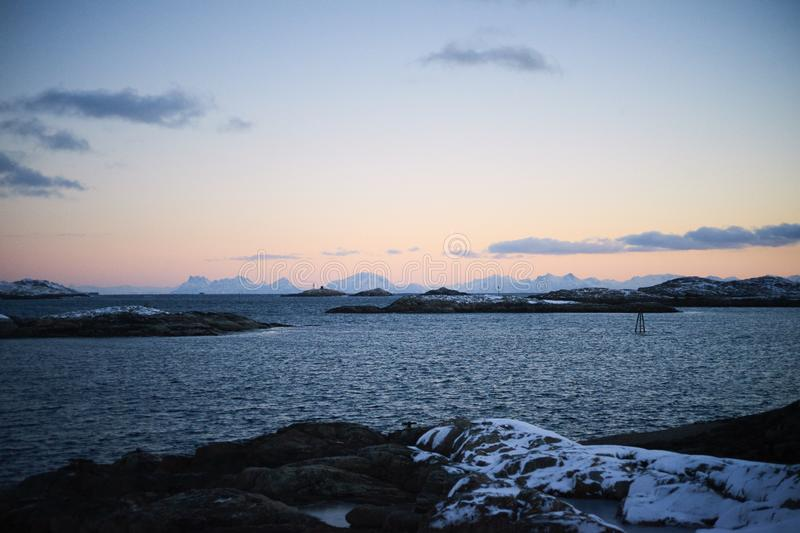 Winter sunset unfrozen sea and low clouds royalty free stock photography