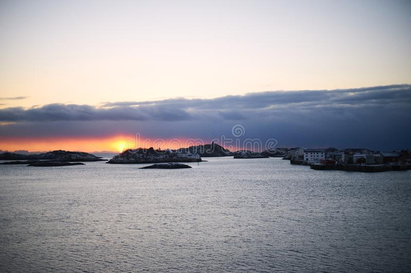 Winter sunset unfrozen sea and low clouds stock photography
