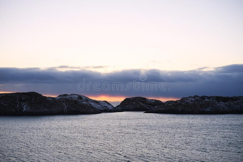 Winter sunset unfrozen sea and low clouds stock photos