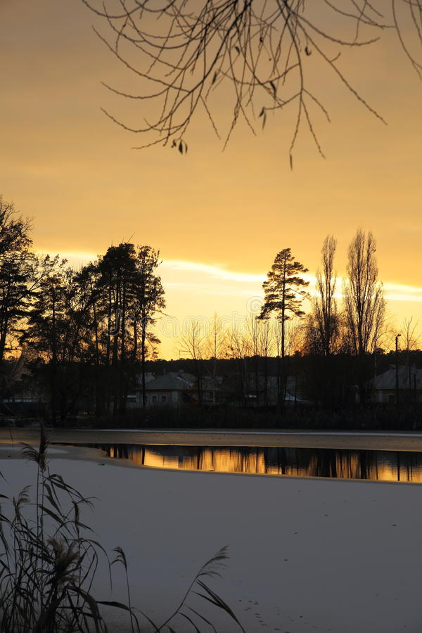 Winter sunset on the village pond. Already gone behind the horizon the sun brightly lit the sky and reflected in the unfrozen water royalty free stock photos