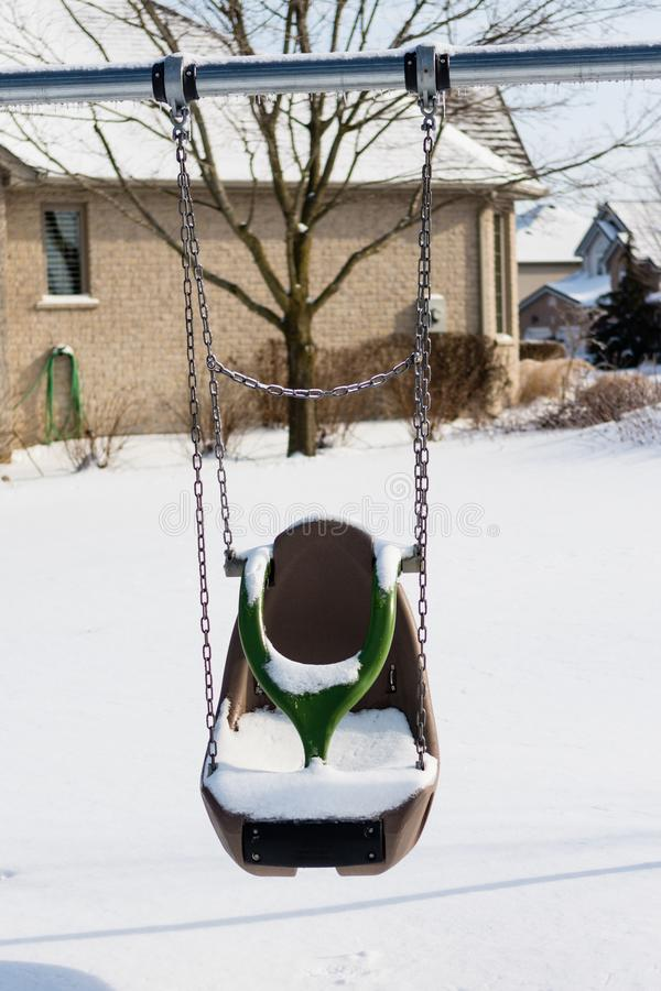 A lone Winter swing. A lone swing covered with snow hangs in anticipation of spring royalty free stock photos
