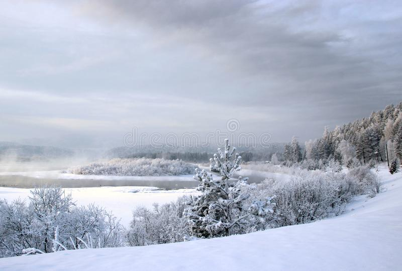 Winter tale of the dream river bend around the island and faint mist over there stock image