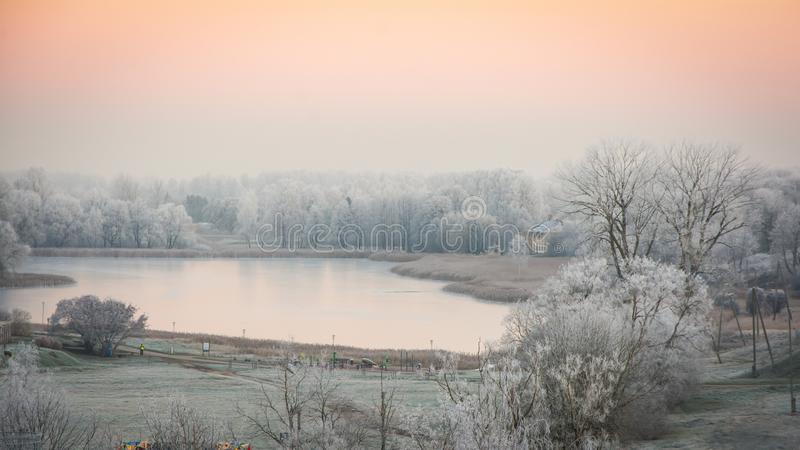 Winter in Talsi, Latvia. Early morning, sunrise. Winter frost. Lake, park, cityscape. Beautiful morning sunset with winter frost on the trees. December, snow stock photography