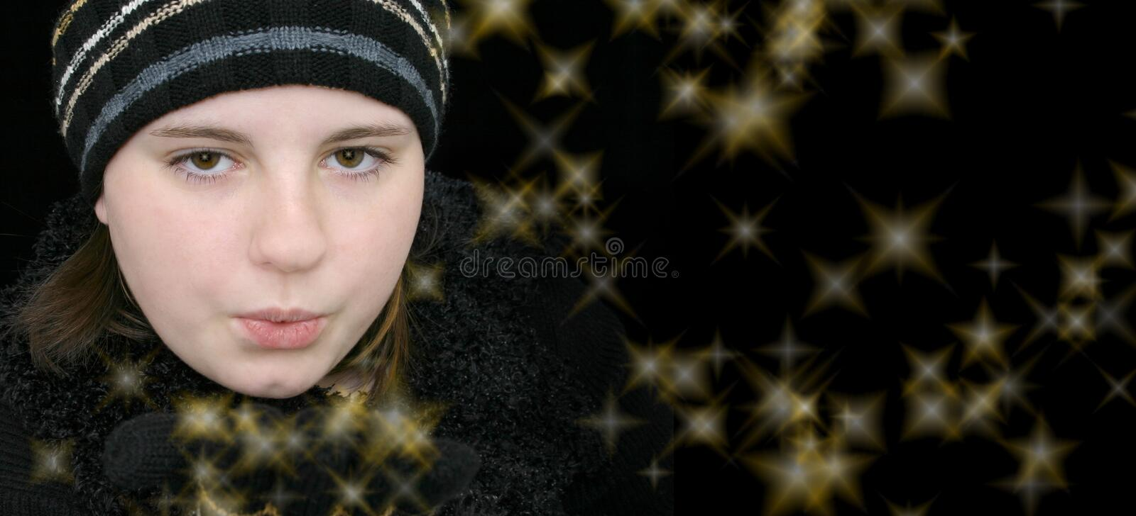 Winter Teen Girl Blowing Magical Stars royalty free stock photo