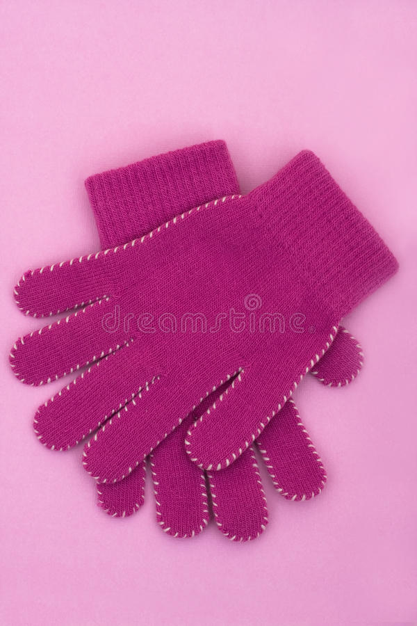 Winter Time. A pair of purple gloves sitting on a purple background, winter time royalty free stock photos