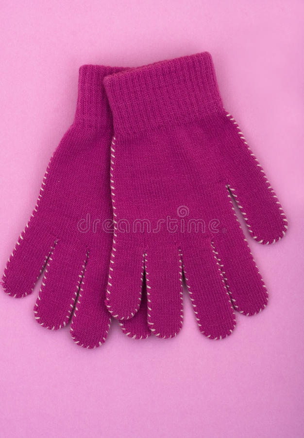 Winter Time. A pair of purple gloves sitting on a purple background, winter time stock image