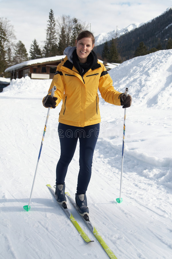 Winter time. A young woman outdoor in a winter setting. The active woman is about to go crosscountry skiing stock photo