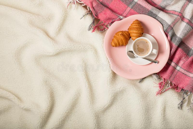 Winter time. A cozy warm pink blanket and a cup of coffee and cr. Oissants on the bed. Selective focus royalty free stock photography