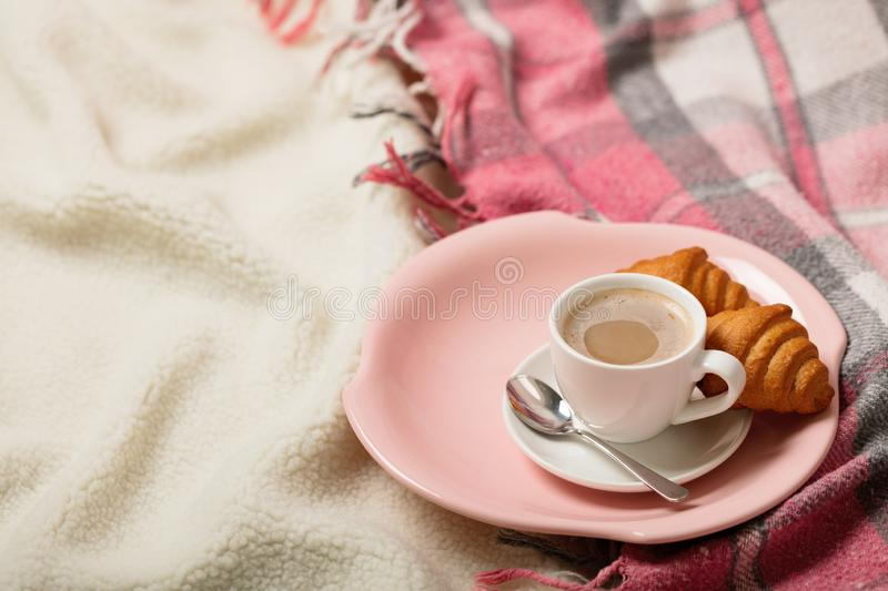 Winter time. A cozy warm pink blanket and a cup of coffee and croissants on the bed. Selective focus royalty free stock photos