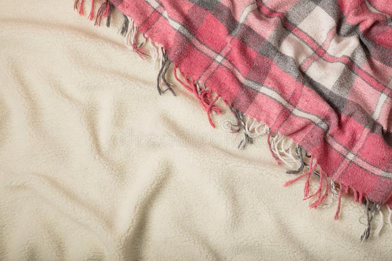 Winter time. A cozy warm pink blanket and a cup of coffee and croissants on the bed. Selective focus royalty free stock image