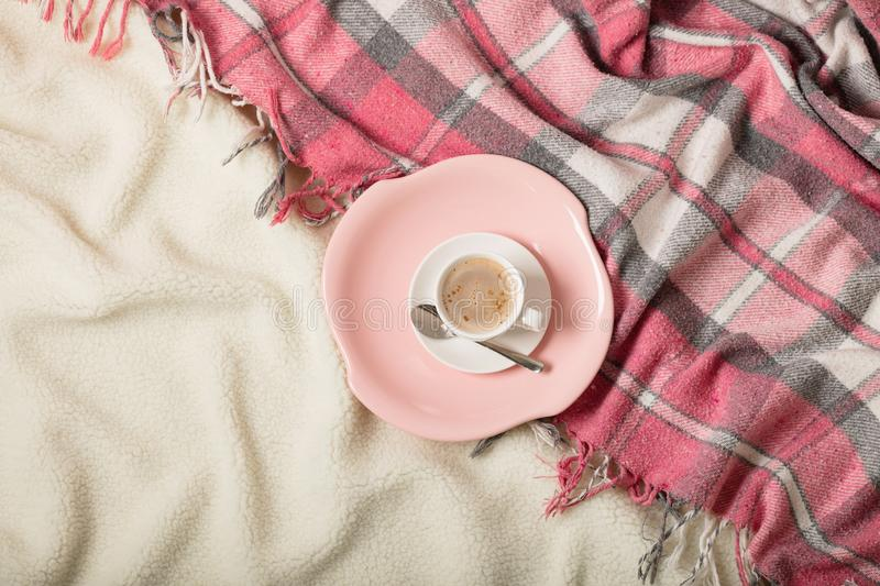Winter time. A cozy warm pink blanket and a cup of coffee and croissants on the bed. Selective focus stock photo