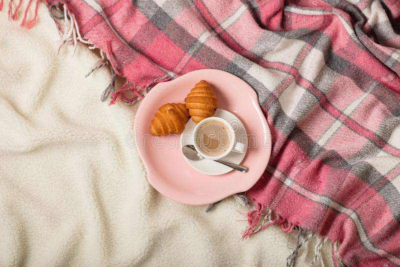 Winter time. A cozy warm pink blanket and a cup of coffee and croissants on the bed. Selective focus stock photos