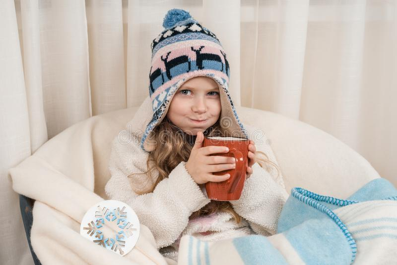 Winter time, little girl at home in an armchair with big cup of hot tea, in warm knitted hat under woolen blanket royalty free stock photo