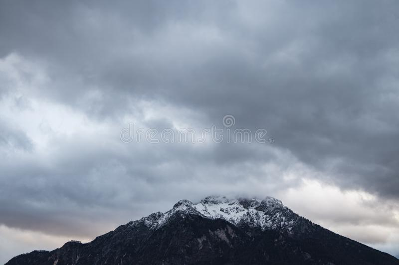 Winter time snowy mountain peak highland dramatic landscape photography moody cloudy sky background, gorgeous nature wallpaper stock image