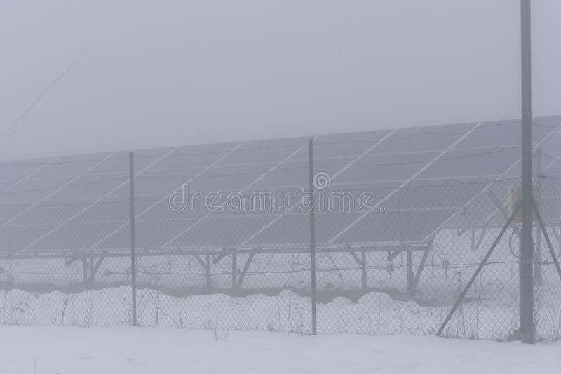 Winter time and solar collectors in fog. And snow stock photo