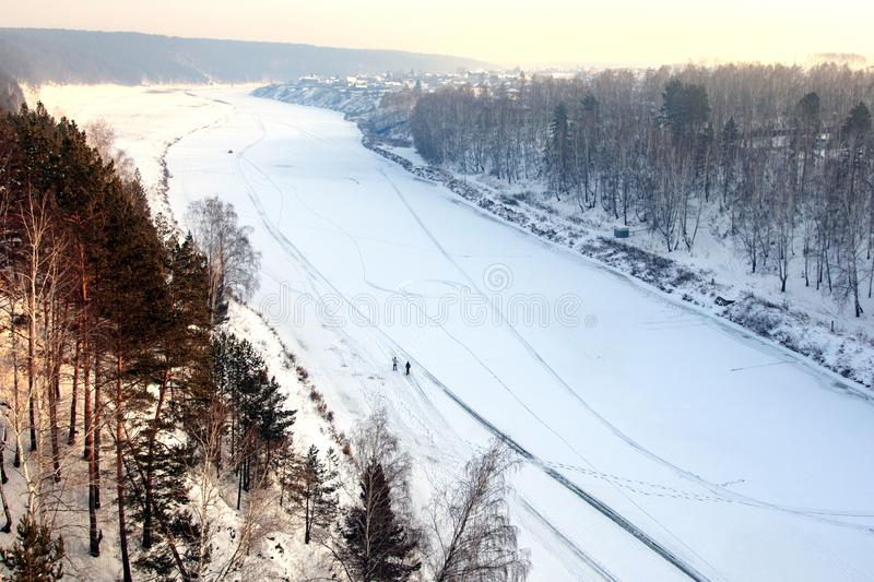 Winter time view from the height of the frozen river, two people on the river snow. And forest stock image