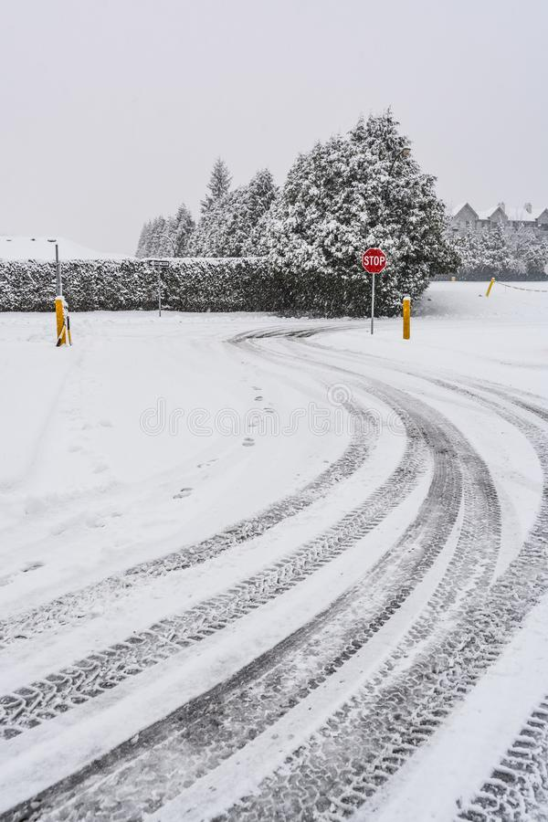 Winter tires traces on snowy road turn with stop sign in front stock photos
