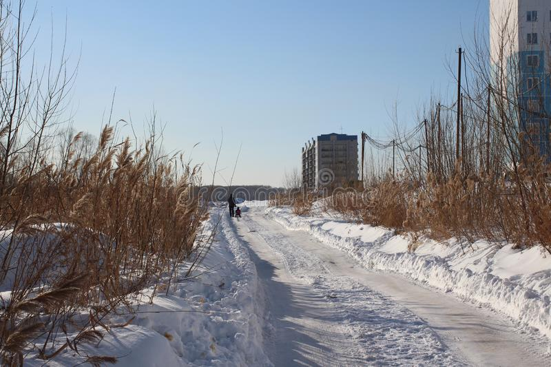 Winter track road high apartment buildings in the city drive through the wasteland royalty free stock photography