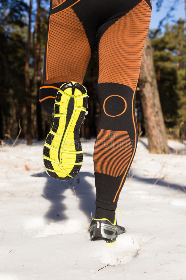 Winter trail running: man takes a run on a snowy mountain path in a pine woods. Winter trail running royalty free stock photography