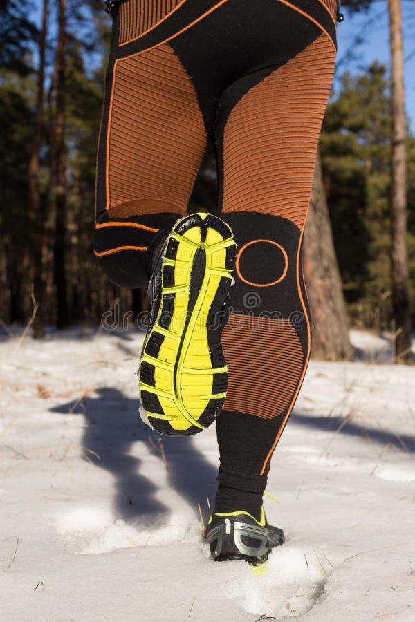 Winter trail running: man takes a run on a snowy mountain path in a pine woods. Winter trail running royalty free stock image