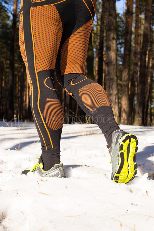 Winter trail running: man takes a run on a snowy mountain path in a pine woods. Winter trail running stock photos