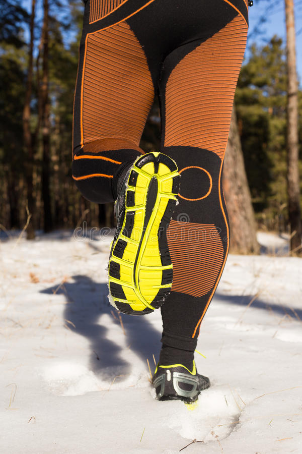 Winter trail running: man takes a run on a snowy mountain path in a pine woods. Running outdoors royalty free stock photo
