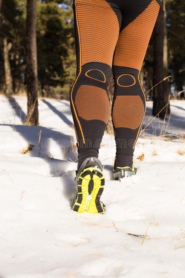 Winter trail running: man takes a run on a snowy mountain path in a pine woods. Running outdoors stock photo